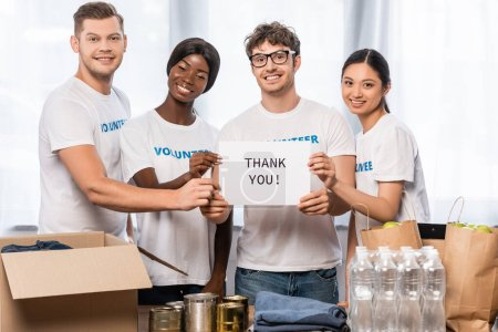 Photo for Multicultural volunteers holding card with thank you lettering beside tin cans, clothes and packages on table - Royalty Free Image