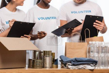 Photo pour Vue recadrée de bénévoles multiethniques avec des presse-papiers près des boîtes de conserve, des vêtements et des paquets dans le centre de bienfaisance - image libre de droit