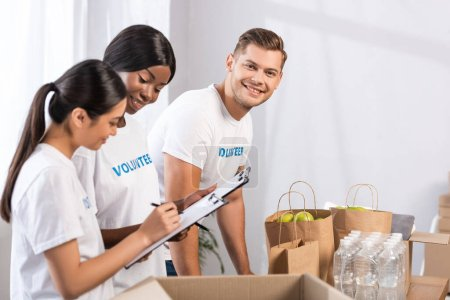 Photo for Selective focus of volunteer looking at camera near multicultural women with clipboards and packages in charity center - Royalty Free Image