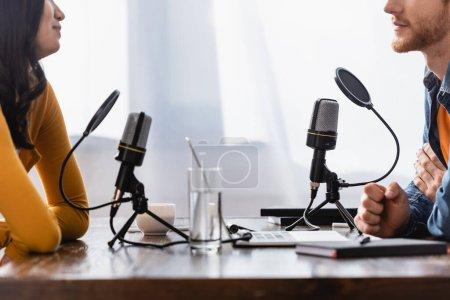 Photo pour Vue partielle de la jeune femme et intervieweur près des microphones dans le studio de radio - image libre de droit