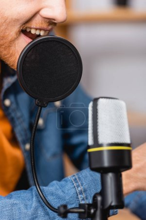cropped view of excited broadcaster speaking in microphone at workplace