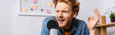 Photo pour Panoramic concept of worried redhead radio host speaking and gesturing near microphone - image libre de droit
