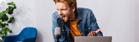 Photo pour Horizontal concept of irritated redhead announcer gesturing while shouting in microphone near laptop - image libre de droit