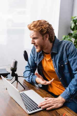 Photo pour Tense broadcaster in denim shirt gesturing while talking in microphone near laptop - image libre de droit