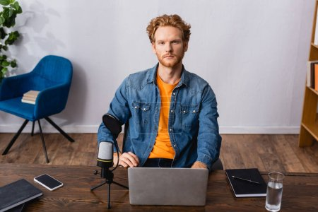 Photo pour Serious announcer in denim shirt sitting at workplace near microphone, gadgets and notebooks - image libre de droit