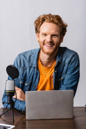 Photo for Excited radio host in denim shirt looking at camera near laptop and microphone - Royalty Free Image