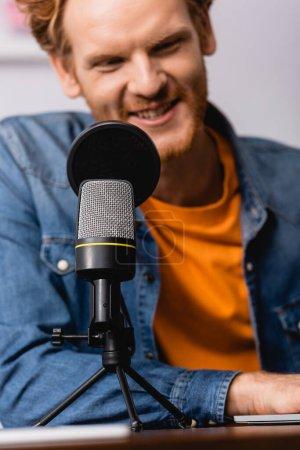 Photo pour Foyer sélectif du jeune annonceur barbu parlant au microphone sur le lieu de travail - image libre de droit