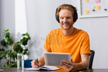 redhead student in wireless headphones using digital table while writing in notebook at home