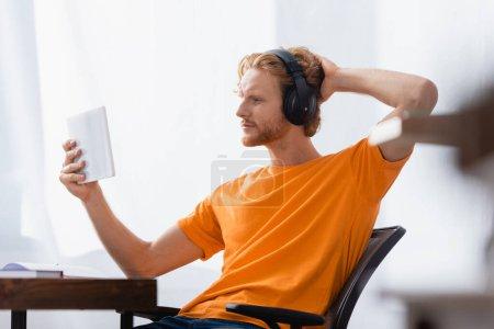 Selektiver Fokus eines verträumten Studenten in drahtlosen Kopfhörern, der den Kopf berührt, während er zu Hause ein digitales Tablet benutzt