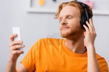Photo pour Foyer sélectif de l'homme rêveur toucher écouteurs sans fil tout en tenant smartphone - image libre de droit