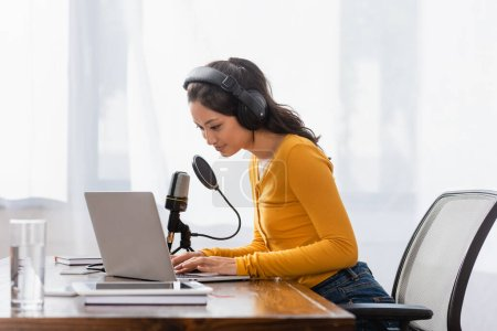 Photo pour Brunette asian announcer in wireless headphones typing on laptop near microphone in studio - image libre de droit