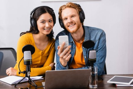 Photo pour Young broadcaster holding smartphone while looking at camera together with asian colleague in radio studio - image libre de droit