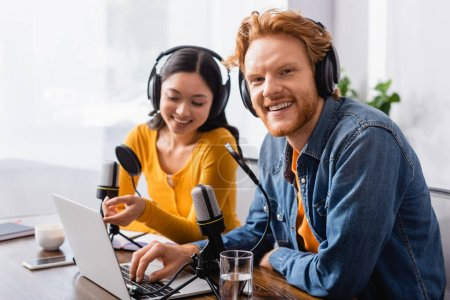 selective focus of asian broadcaster pointing with finger at laptop near excited colleague in wireless headphones