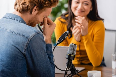 Photo for Selective focus of excited asian radio host looking at confused man touching face during interview - Royalty Free Image