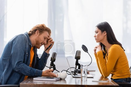 Photo pour Young asian radio host looking at tense man touching head during interview in studio - image libre de droit