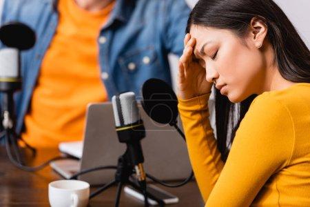 Photo pour Foyer sélectif de radio hôte près bouleversé asiatique femme toucher la tête au cours de l'interview - image libre de droit