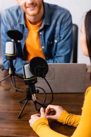 Photo pour Vue partielle de l'animateur radio interviewant une femme près de microphones et ordinateur portable en studio - image libre de droit