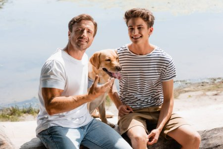 padre e hijo sentado con golden retriever cerca del lago