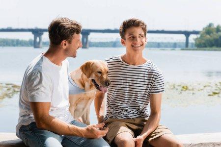 Photo pour Père regardant heureux fils près golden retriever et rivière - image libre de droit