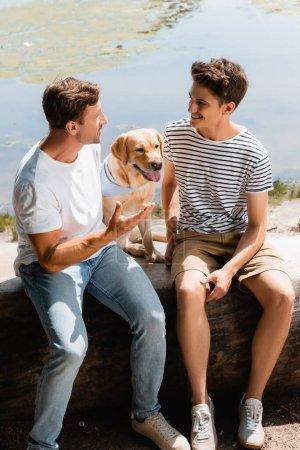 Photo pour Père et fils se regardant tout en parlant près de golden retriever et lac - image libre de droit