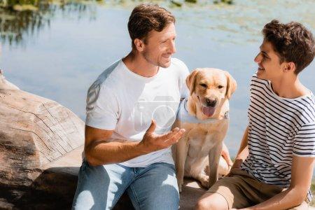 Photo pour Père et fils regardant l'autre tout en étant assis près golden retriever et lac - image libre de droit