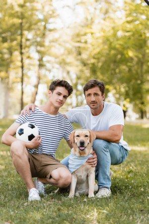 Photo pour Père assis près de fils adolescent avec football et golden retriever - image libre de droit