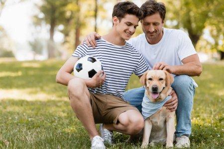 Photo pour Père assis près de fils adolescent avec football câlin golden retriever - image libre de droit