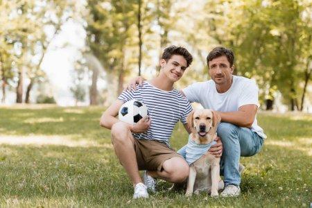 Photo pour Père assis près de heureux fils adolescent avec football et golden retriever - image libre de droit
