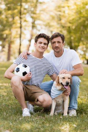 Photo pour Père assis sur l'herbe près de fils adolescent avec football et golden retriever - image libre de droit