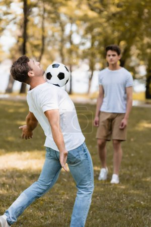 Photo for Selective focus of father playing football with teenager son - Royalty Free Image