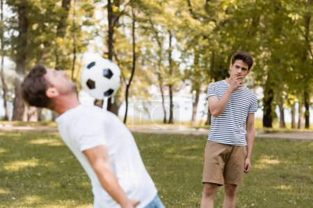 selective focus of pensive teenager son looking at father playing football