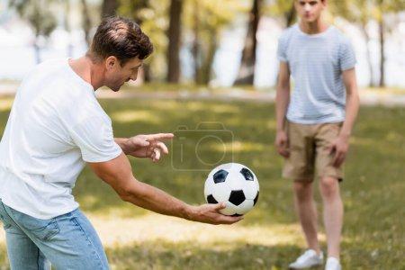 Selektiver Fokus des Vaters, der den Fußball in der Hand hält, in der Nähe von Teenagersohn