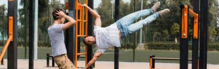 Teenager-Sohn berührt Kopf beim Sport-Vater-Turnen am Reck
