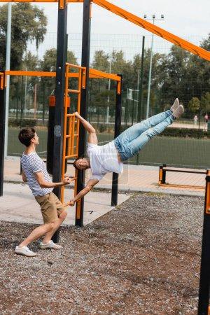 nastolatek syn wskazując z ręki patrząc na sportowe ojciec ćwiczenia na poziome pręty