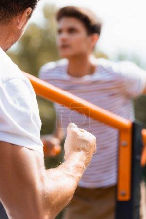 Photo pour Foyer sélectif du père avec le poing serré près du fils adolescent exerçant sur les barres horizontales - image libre de droit