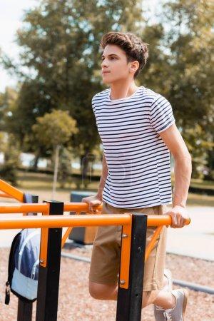 Photo pour Sportive teenager boy exercising on horizontal bars - image libre de droit