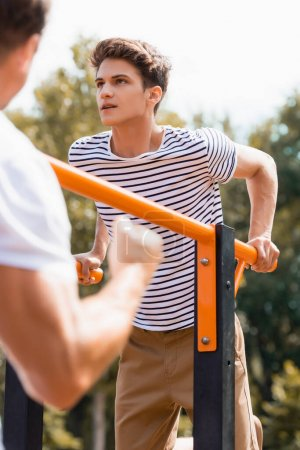 selective focus of teenager boy exercising on horizontal bars near father