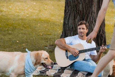 Photo pour Foyer sélectif de père assis sous l'arbre et jouer de la guitare acoustique tout en regardant adolescent fils et golden retriever - image libre de droit