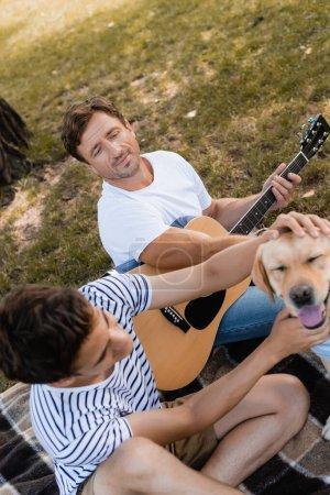 Photo pour Homme tenant guitare acoustique et câlins golden retriever avec fils adolescent - image libre de droit