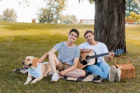 Photo pour Adolescent garçon et père assis sur couverture près golden retriever sous tronc d'arbre - image libre de droit