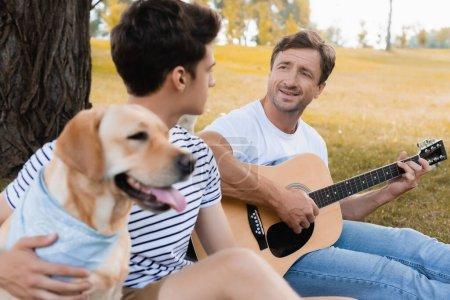 Photo pour Foyer sélectif de l'homme jouant de la guitare acoustique près de fils adolescent et golden retriever dans le parc - image libre de droit