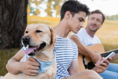 selektywne skupienie golden retriever w pobliżu nastolatka z smartphone i mężczyzna trzyma gitarę akustyczną w parku