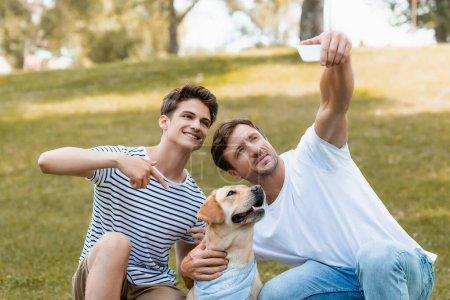 Photo pour Adolescent garçon pointant avec doigt à golden retriever tandis que père prendre selfie - image libre de droit