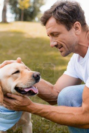 Photo pour Homme en t-shirt blanc câlin doré retriever dans le parc - image libre de droit