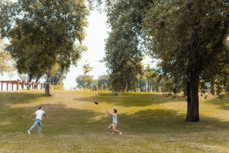 Photo for Father and teenager son playing american football in green park - Royalty Free Image