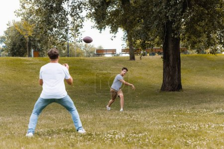 selective focus of teenager boy playing american football with father in green park