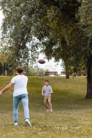 Photo pour Vue arrière du père lançant la balle de rugby au fils adolescent dans le parc vert - image libre de droit