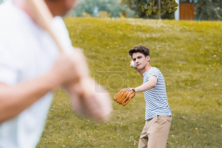 selective focus of teenager boy in leather glove holding ball while playing baseball with father