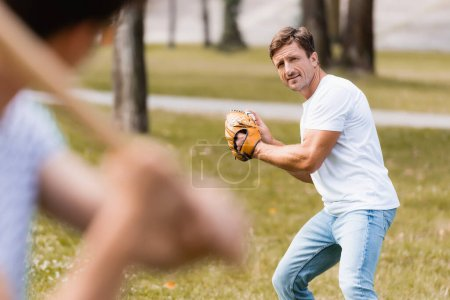 selective focus of concentrated father in leather glove playing baseball with teenager son in park