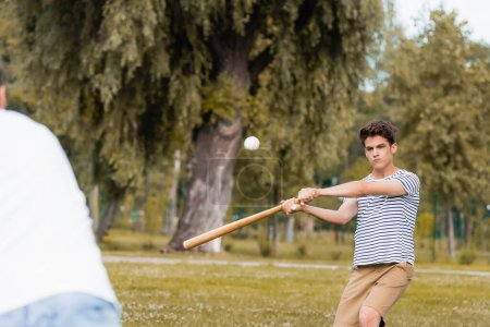Photo pour Selective focus of teenager boy with softball bat playing baseball with father in park - image libre de droit